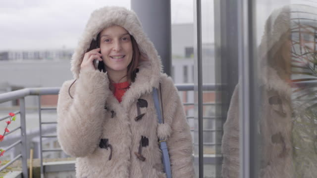 a young woman on the phone, on a balcony in winter. - winter coat stock videos & royalty-free footage