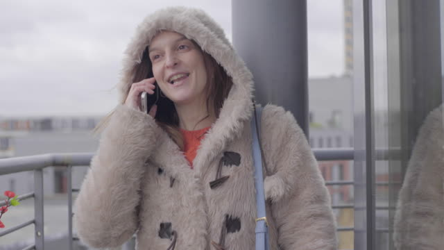 A young woman on the phone, on a balcony in winter.