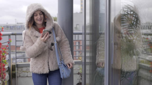 a young woman on the phone, on a balcony in winter. - purse stock videos & royalty-free footage
