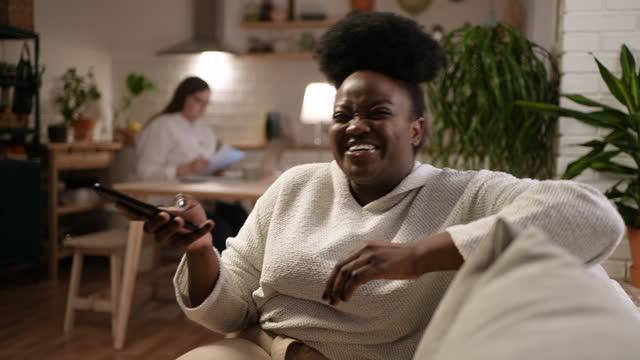 vídeos de stock, filmes e b-roll de jovem em chamada de vídeo com sua família ou amigos enquanto seu companheiro de quarto trabalha em um laptop ao fundo - amizade feminina