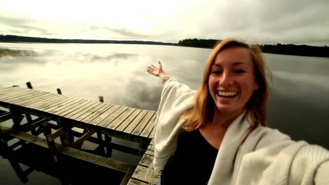 young woman on wooden wharf above lake, takes selfie portrait - jetty stock videos & royalty-free footage