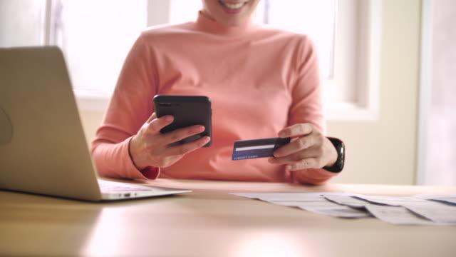 vídeos y material grabado en eventos de stock de banca en línea joven usando el teléfono inteligente de compras online con tarjeta de crédito en casa - t mobile