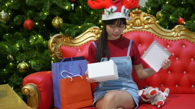 junge Frau öffnen Weihnachtsgeschenk auf roten sofa