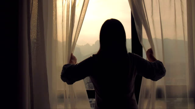 young woman open curtain in the morning - looking through window stock videos & royalty-free footage