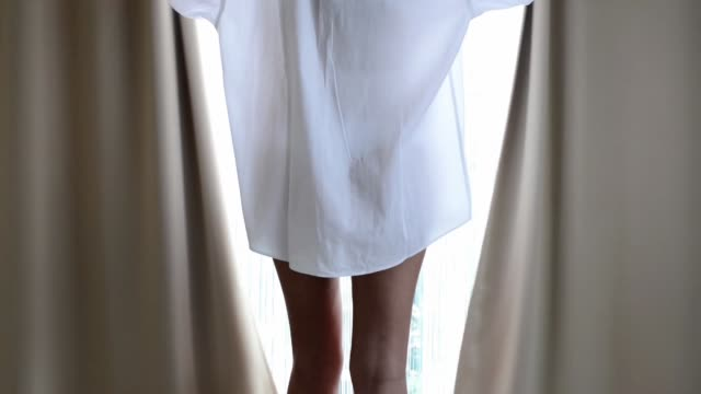 young woman open curtains and standing near the window in hotel. - limb body part stock videos & royalty-free footage