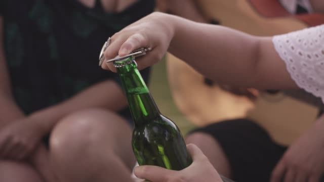 young woman opening a bottle of beer - bottle opener stock videos & royalty-free footage
