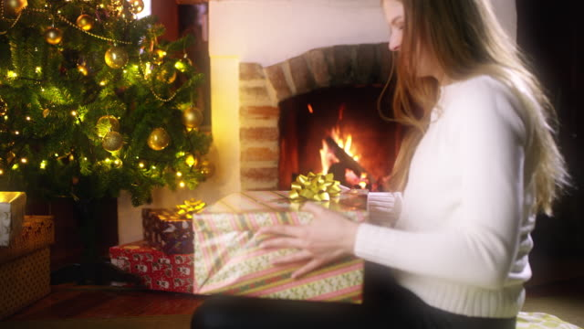 ds young woman opening a christmas present - 18 23 months video stock e b–roll