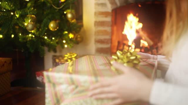 ds ms junge frau öffnet ein weihnachtsgeschenk - 18 23 monate stock-videos und b-roll-filmmaterial