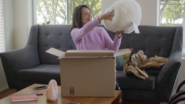 young woman opening a delivery box at home - opening stock videos & royalty-free footage