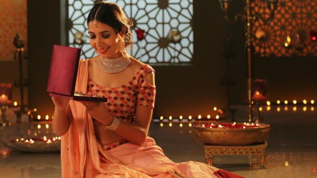 MS Young woman opening a jewellery box during Diwali festival / New Delhi, Delhi, India