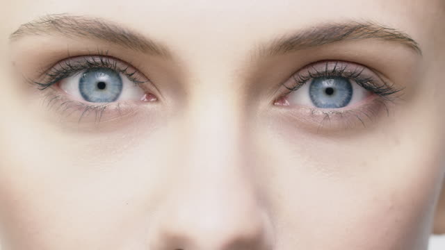 young woman opening and closing her blue eyes - eyelid stock videos and b-roll footage