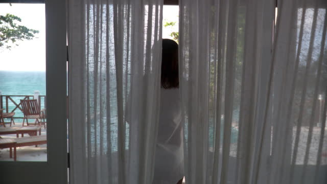 ms young woman opening door between white curtains, walking out to pool and dipping feet in water/ scarborough, tobago, trinidad and tobago - walking in water stock videos & royalty-free footage