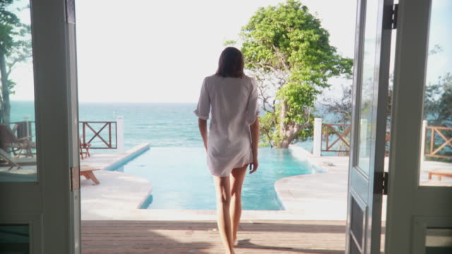ws young woman opening double doors, walking out to infinity pool and dipping feet in water before walking back indoors and smiling at camera/ scarborough, tobago, trinidad and tobago - walking in water stock videos & royalty-free footage