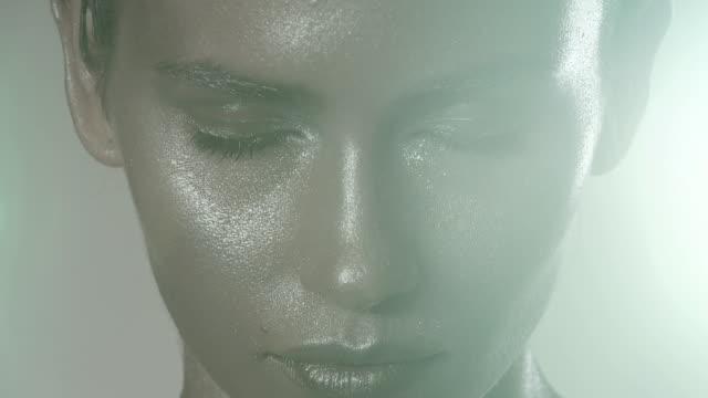 vídeos de stock, filmes e b-roll de young woman opening eyes, metallic make up on face - obscured face