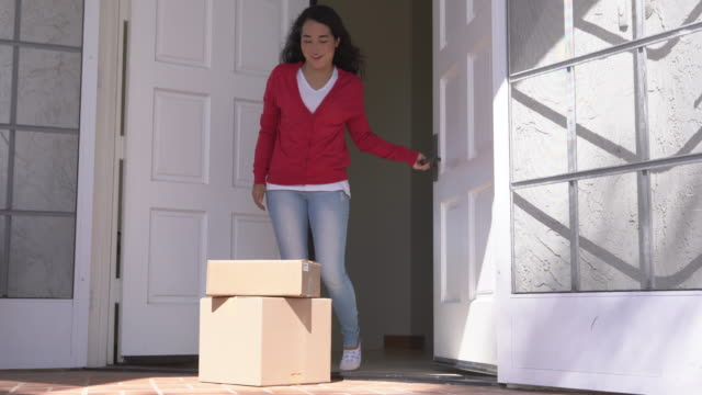 WS Young woman opening her door and picking up packeges
