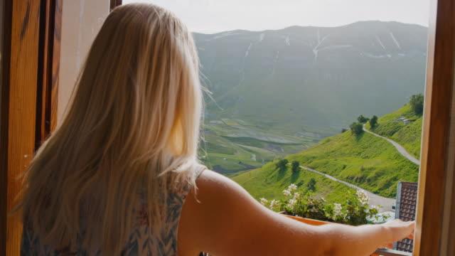 vídeos de stock, filmes e b-roll de ms jovem mulher abrindo persianas de hotel para ensolarada e tranquila vista da montanha, castelluccio, úmbria, itália - olhar para vista