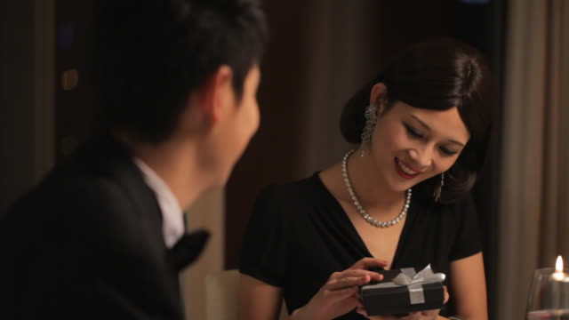 MS Young woman opening present during candle lit dinner / China