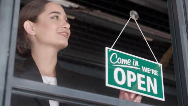 vídeos y material grabado en eventos de stock de joven, apertura de la tienda - señal de abierto