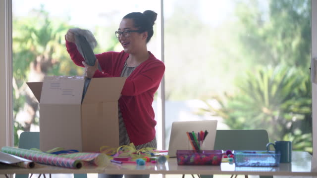 MS young woman opening up a box at her desk