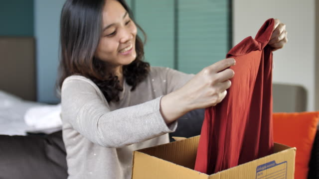 Young Woman Opens Cardboard Box at home