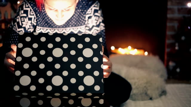 young woman opens Christmas present