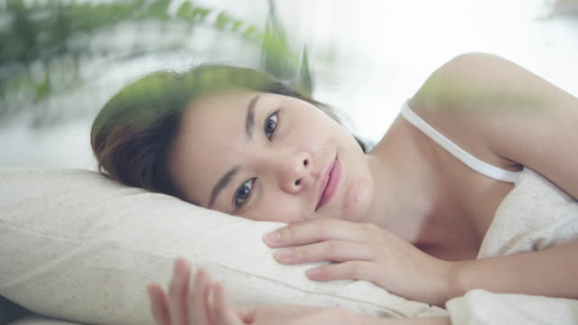 young woman opens her eyes on a sunny morning. - nightwear stock videos & royalty-free footage