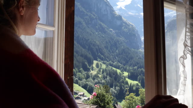 young woman opens window, looks out to mountain scene - shawl stock videos & royalty-free footage