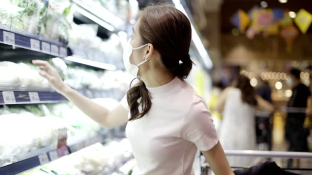 vidéos et rushes de jeune femme ou fille utilisant un masque facial achetant la nourriture dans le supermarché - cadrage aux genoux