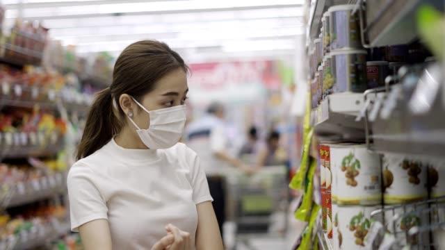 vídeos de stock, filmes e b-roll de jovem ou menina usando uma máscara facial comprando comida em supermercado - mercado espaço de venda no varejo