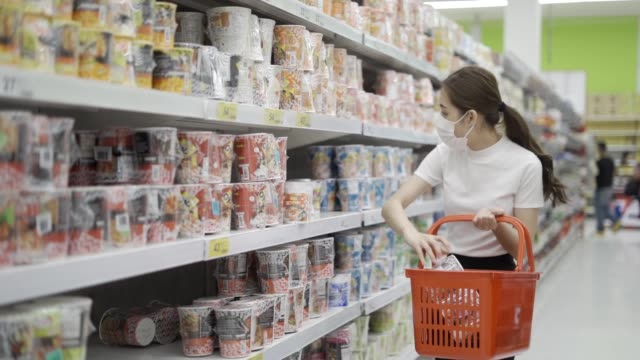 young woman or girl wearing a facial mask buying food in supermarket - three quarter length stock videos & royalty-free footage