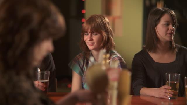 vídeos y material grabado en eventos de stock de ms pan young woman ordering beer sitting and talking to man in bar, brooklyn, new york city, new york state, usa - encargar
