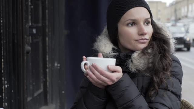 a young woman outside a cafe during winter. - woolly hat stock videos and b-roll footage