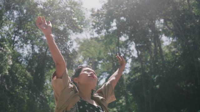vídeos y material grabado en eventos de stock de mujer joven outstretching brazos frente a cascada - miembro humano