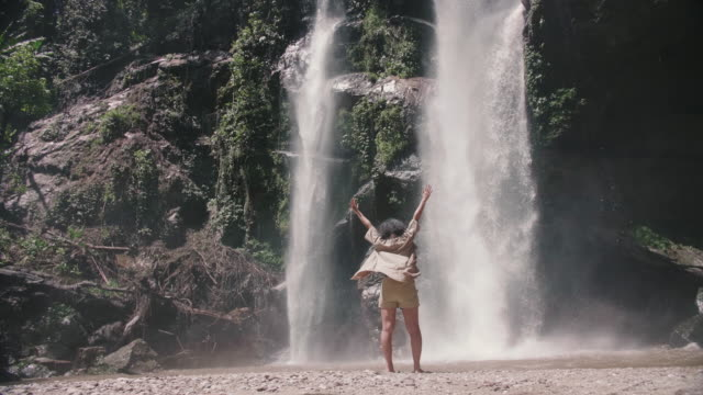 young woman outstretching arms in victory in front of waterfall - human limb stock videos & royalty-free footage