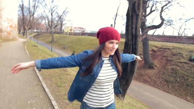 vídeos de stock, filmes e b-roll de mulher jovem outstretching os braços enquanto uma caminhada no parque. - de braço levantado