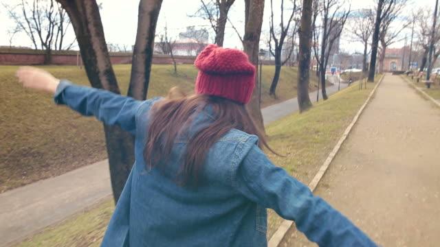 Junge Frau ausweitende Ihre Arme, während Fuß im Park.