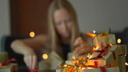 A young woman pack presents. She is tired of making so many presents prior to big holidays. Concept of tiredness from the Christmas and New year