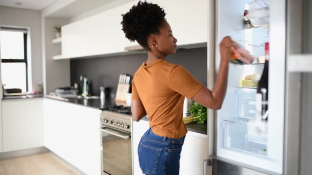 young woman packing groceries at the fridge - refrigerator stock videos & royalty-free footage