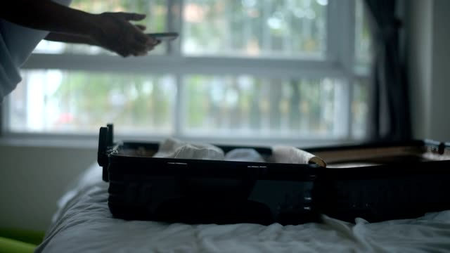 young woman packing suitcase at home. - bagaglio video stock e b–roll
