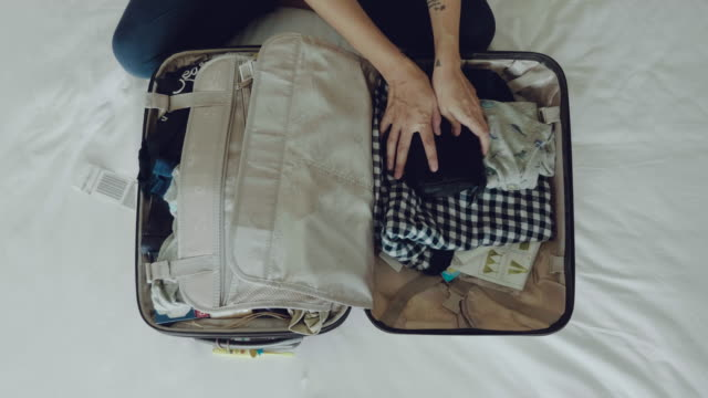 young woman packing suitcase - bagaglio video stock e b–roll