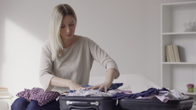 young woman packing suitcase - packing stock videos and b-roll footage