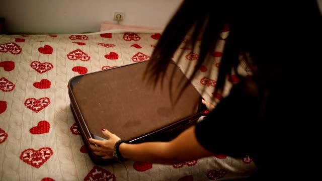 vídeos de stock, filmes e b-roll de jovem embala uma mala para a viagem em seu quarto - bagagem