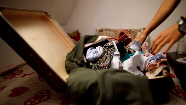 vidéos et rushes de la jeune femme emballe une valise pour le voyage dans sa chambre - valise
