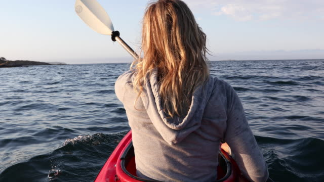 young woman paddles ocean kayak at sunrise - hooded top stock videos & royalty-free footage