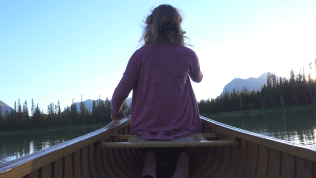 young woman paddles wooden canoe into mountain lake - pagaiare video stock e b–roll