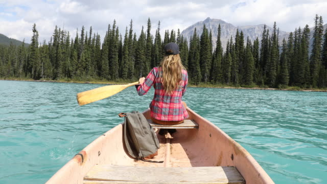 stockvideo's en b-roll-footage met a young woman paddling a canoe across a high alpine lake. - rear view