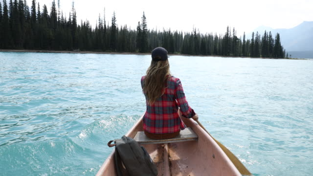 a young woman paddling a canoe across a high alpine lake. - タータンチェック点の映像素材/bロール