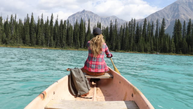 vídeos de stock, filmes e b-roll de a young woman paddling a canoe across a high alpine lake. - canoagem
