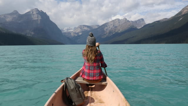 a young woman paddling a canoe across a high alpine lake. - rudern stock-videos und b-roll-filmmaterial