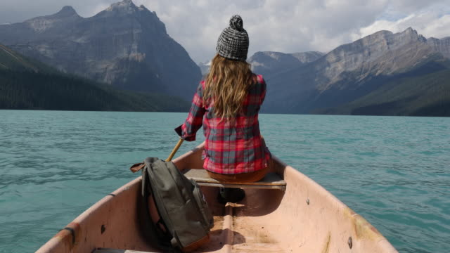 A young woman paddling a canoe across a high alpine lake.